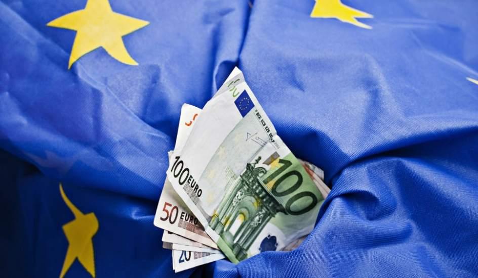 євро купюри на фоні прапору ЄС Євросоюз Україна